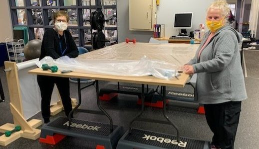 Julie Modesto and Lily White practice social distancing while working on isolation gowns at a Personal Protective Gear workstation in Franciscan Health Fitness Centers Chesterton